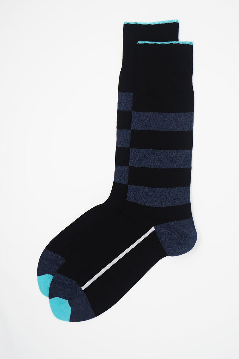 A pair of black equilibrium men's luxury socks by Peper Harow, featuring a white stripe along the foot, and three navy stripes down the calf and on the heel and toe