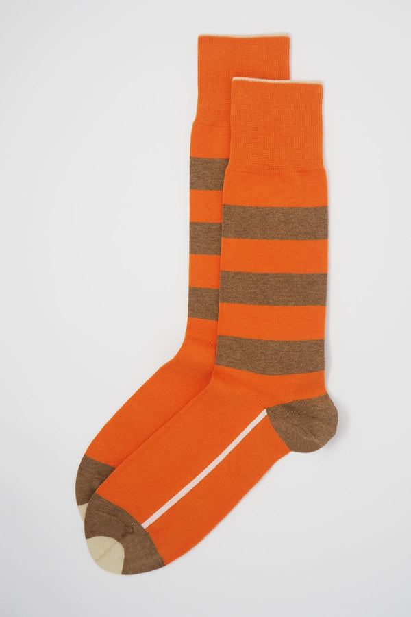 A pair of orange equilibrium men's luxury socks by Peper Harow, featuring a white stripe along the foot, and three brown stripes down the calf and on the heel and toe