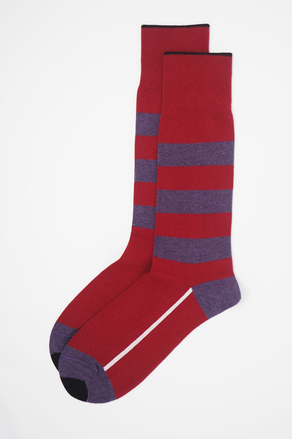 A pair of red equilibrium men's luxury socks by Peper Harow, featuring a white stripe along the foot, and three purple stripes down the calf and on the heel and toe