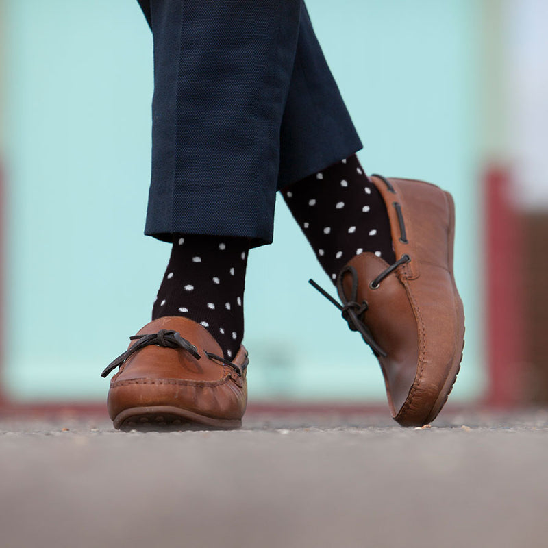 Man standing in smart trousers and smart leather shoes wearing black Pin Polka luxury men's socks by Peper Harow