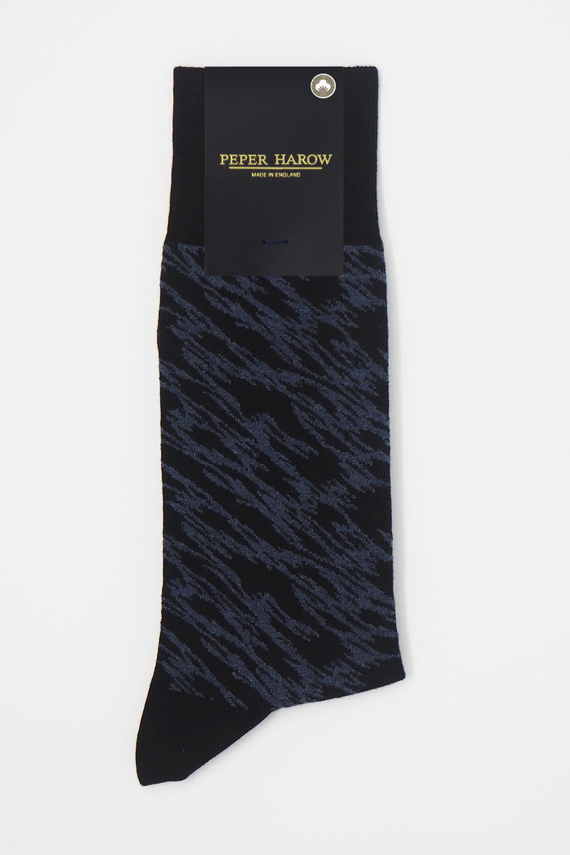 Pandemonium black men's luxury socks by Peper Harow, featuring a quirky navy pattern and navy toe and heel in packaging.