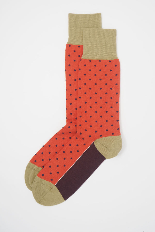 A pair of orange pin polka men's socks with purple polka dots and a beige heel, toe and cuff