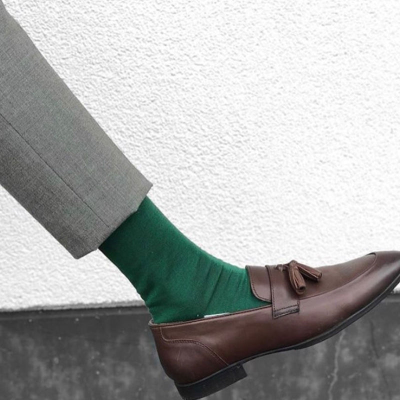 Man in grey trousers and brown loafers wearing Peper Harow emerald Square Mile luxury socks