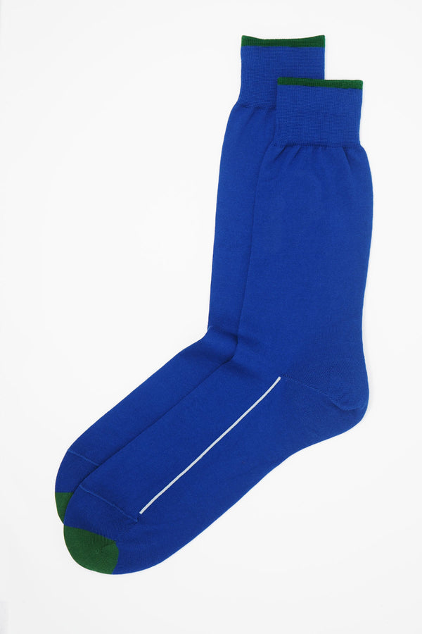 A pair of cobalt blue square mile men's socks with a green toe and cuff line, and a white line down the side of the foot