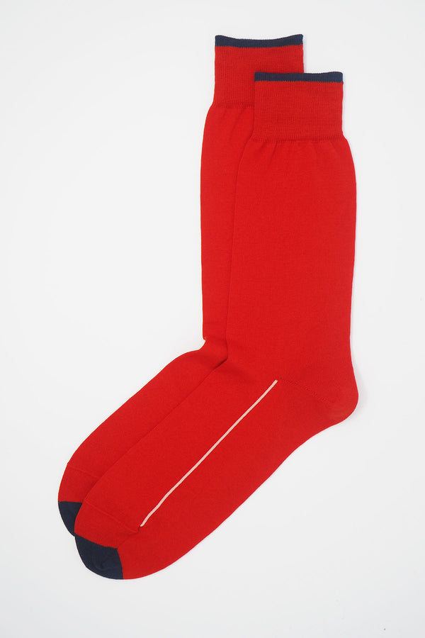 A pair of Cinnabar red square mile men's socks with a navy toe and cuff line, and a white line down the side of the foot