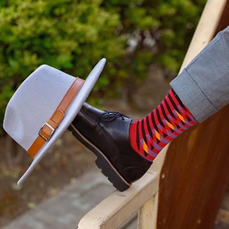 Stylish man wearing Peper Harow Red Symmetry Organic Cotton Socks with a hat on his shoe