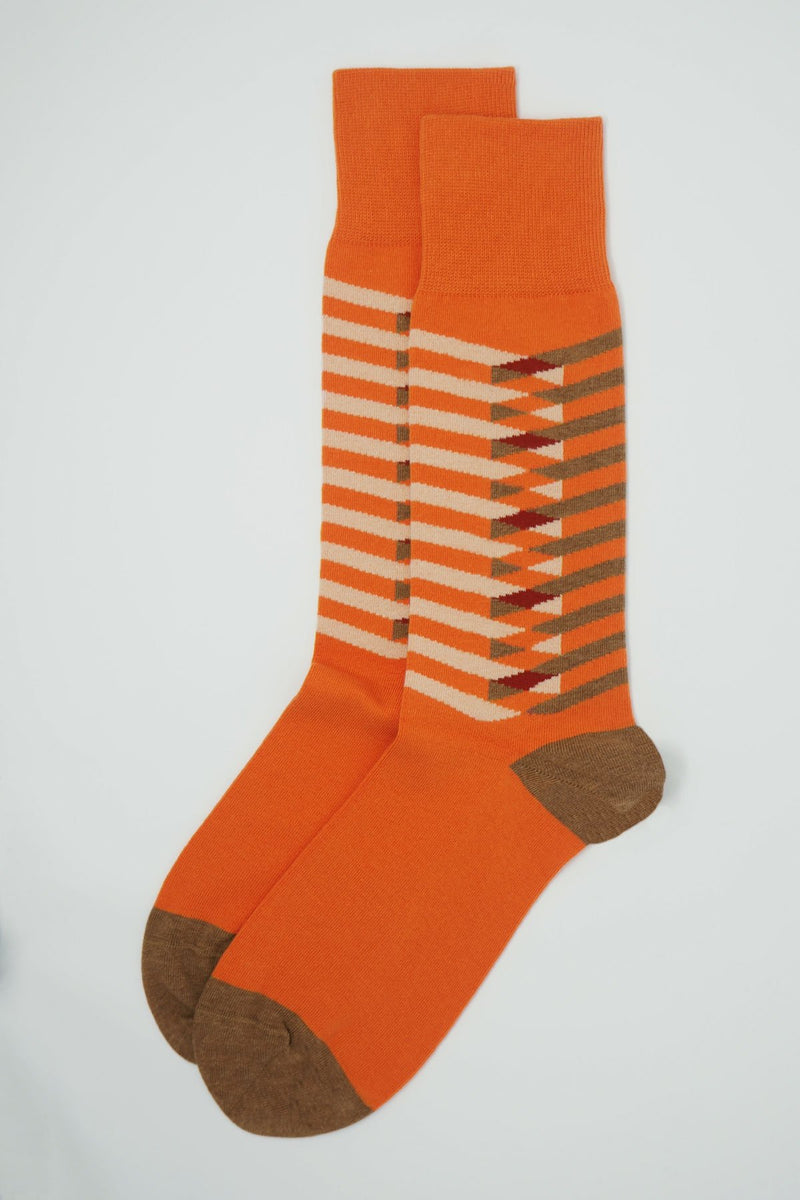 A pair of Symmetry orange men's luxury socks by Peper Harow, featuring stylish brown and white stripes, and a brown heel and toe.