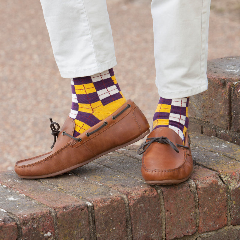 Man standing on a wall wearing brown boat shoes and Peper Harow gold checkmate luxury men's socks
