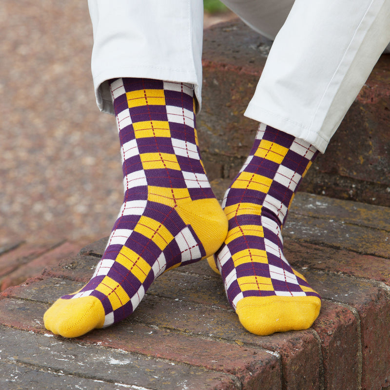 Man sitting on a brick wall wearing Peper Harow gold checkmate men's luxury socks