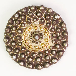 Circle pin with white sapphires and 18 karat gold accents