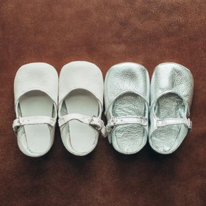 white leather crib shoes, single strap, next to silver leather crib shoes, single strap