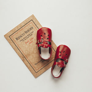 red leather crib shoes, two straps, petal shaped holes, white insides