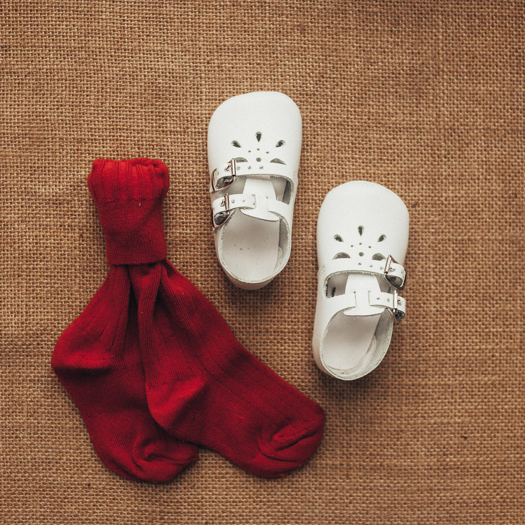 white leather crib shoes, two straps, petal shaped holes, white insides