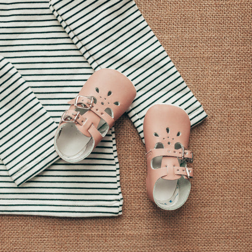 pink leather crib shoes, two straps, petal shaped holes, white insides