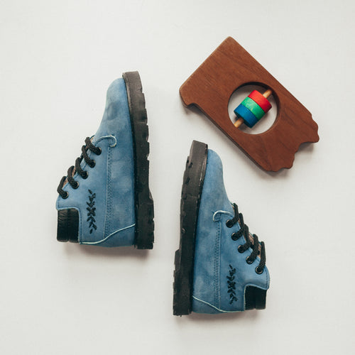 blue nubuck leather boots, black laces, black sole, black cuff around top of shoe, black embroidery on outer side of shoe