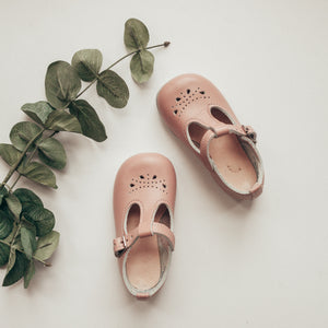 pink leather t-strap, petal shaped holes, single strap, beige inside