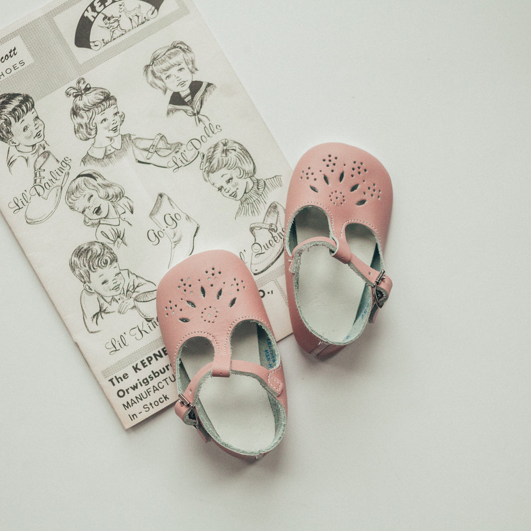 pink leather crib shoes, t-strap, single straps, petal shaped holes, white insides