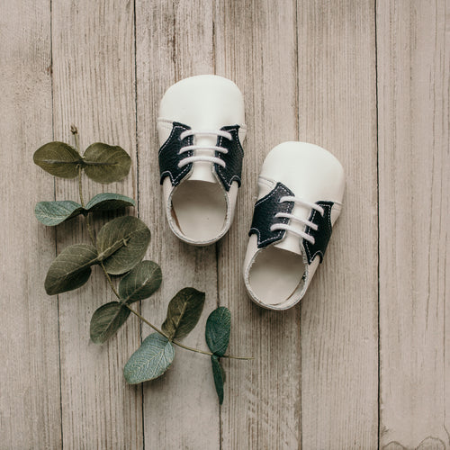 white and navy leather crib shoes, white laces