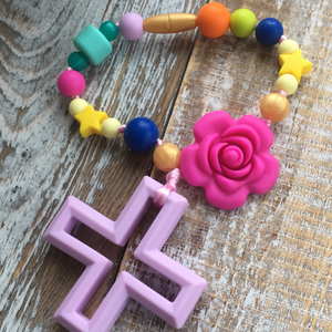 Baby girl teether with rose and cross; bright, vibrant girly colors