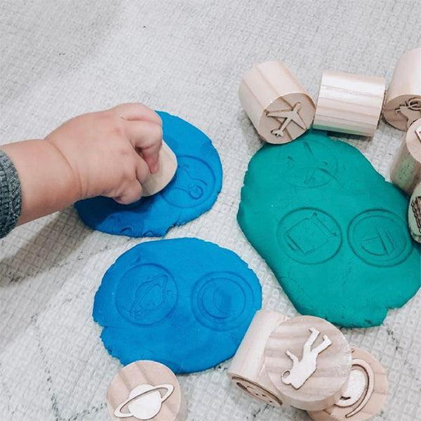 Child playing with playdough stamps