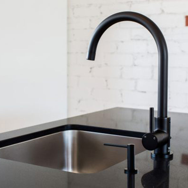 Meir Round Matte Black Soap Dispenser Featured in a Kitchen on a Black Benchtop - The Blue Space