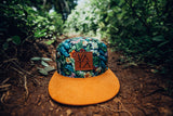 Green and suede Floral Flat Brim Hat with leather strapback and leather logo patch on front sitting on ground in the jungle