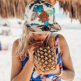 Girl wearing blue and white floral snapback hat drinking from a coconut