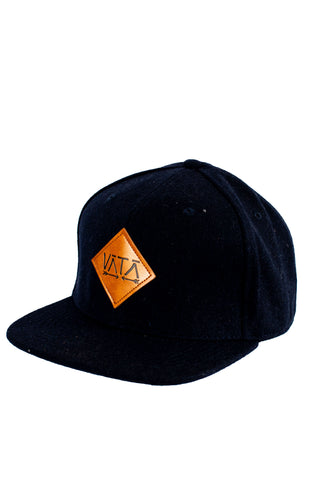 Navy blue textured snapback flat brim hat with brown leather logo on front that says VATA