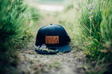 Navy blue textured snapback flat brim hat with brown leather logo on front that says VATA sitting in grass