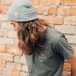 man with long hair in a grey beanie posing in a t-shirt with a mountain logo