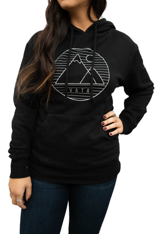Woman wearing Black Hoodie with white mountain VATA logo on front