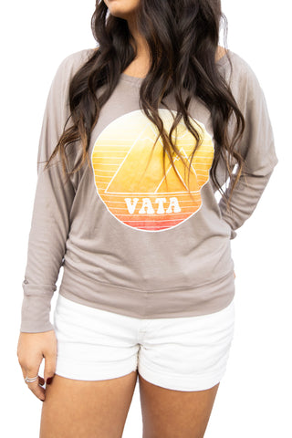 Woman wearing long sleeve T-shirt with VATA Mountain logo on front in yellow-orange