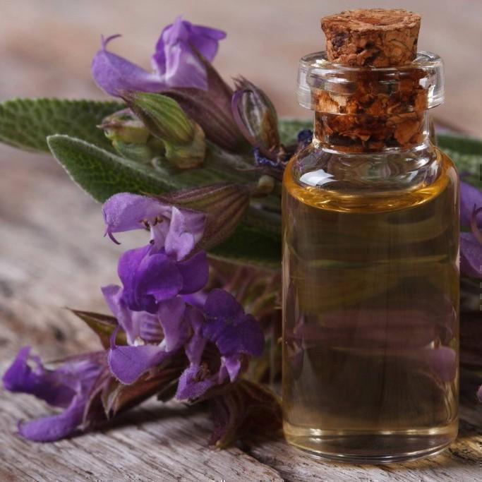 Clary Sage essential oil with clary sage flowers in the background