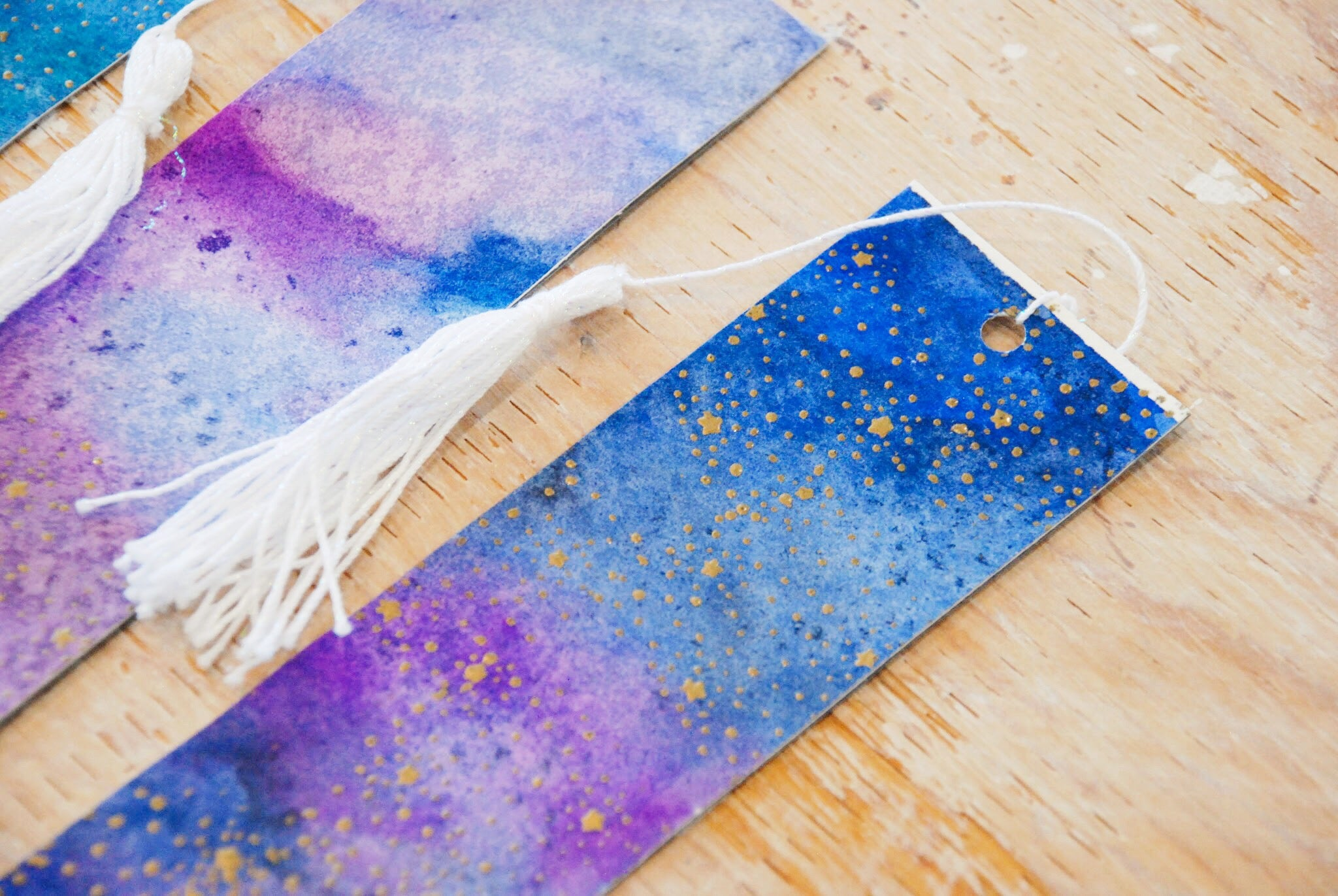 Galaxy Away | handmade bookmarks with handmade tassels | blue-purple-pink-green galaxy background with gold embossed stars and white glitter tassel | Thoughtfully Handmade