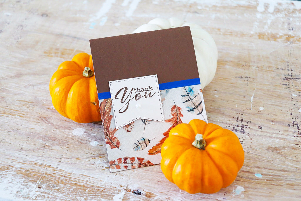 Autumn | handmade thank you card | dark brown card base with orange feather pattern paper at bottom, lined with navy washi tape | banner with thank you sentiment | Thoughtfully Handmade