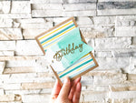 Birthday Bonanza | Stripes variant | handmade birthday card | teal & yellow striped background with sage green watercolour tag | happy birthday sentiment | Thoughtfully Handmade