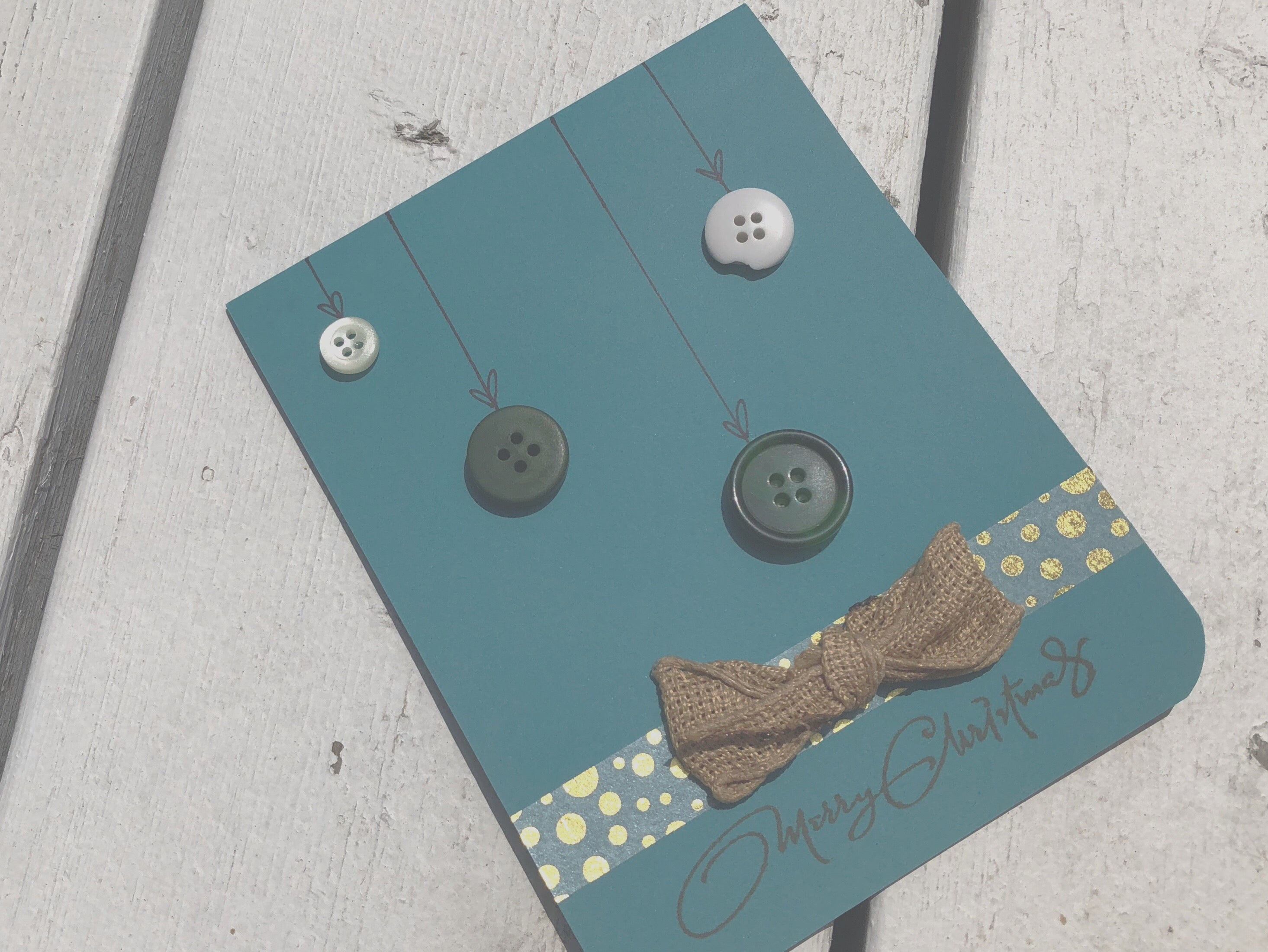 Buttons n' Baubles | handmade Christmas card | turquoise variant | 3 button ornaments hanging from top, washi tape stripe at bottom with burlap bow | merry christmas sentiment at bottom | Thoughtfully Handmade
