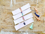 Watercolour Madness | Purple Variant | Handmade Watercolour Bookmarks | purple watercolour background with various designs on it | coral, navy or mint green tassels | Thoughtfully Handmade