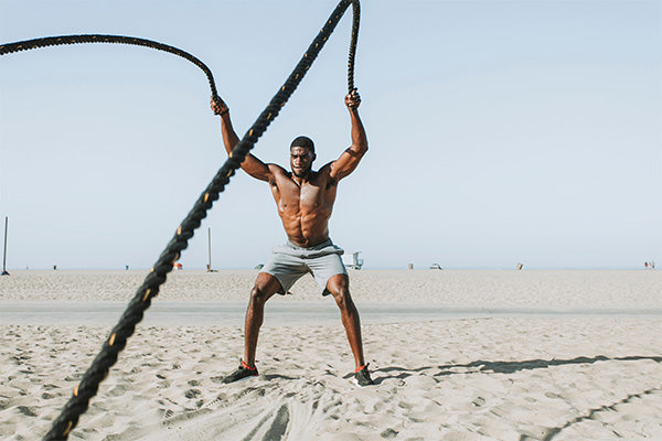man using battle ropes