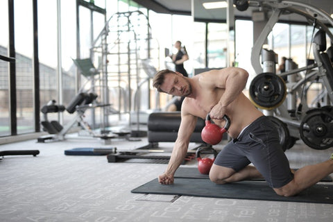 man working with kettlebell in gym