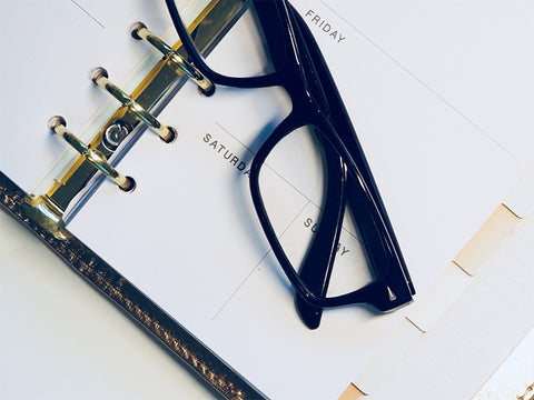 weekly planner and black glasses