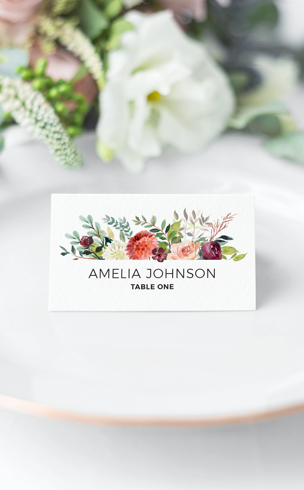 Burgundy floral seating card on white plate at Wedding reception