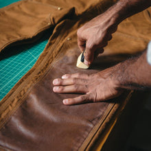 image of otter wax being applied to a pair of overalls