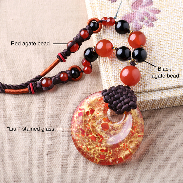 the necklace is made of stained glass, and black and red agate beads