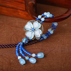 blue long necklace, with Oriental style decorations, and blue crystals organized into shape of a lucky clover leaf.
