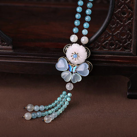 blue long necklace, with Oriental style butterfly decorations, blue crystals, and white jade