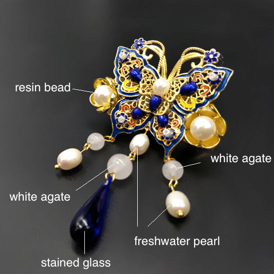 The pin is made with white agate, strained agate, freshwater pearls, and quality metal parts