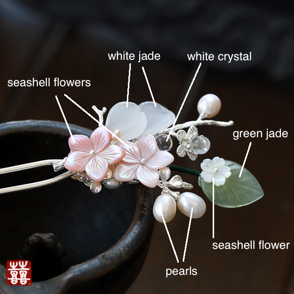 the hairpin is decorated with seashell flowers, white jade, white crystal, green jade and freshwater pearls