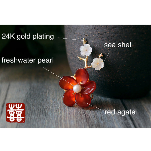 This flower brooch is made of red agate, seashell, freshwater pearls and 24K gold plated metal parts