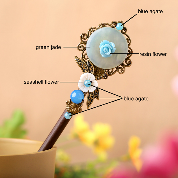 the hair stick is made of wood, decorated with green jade, seashell, and blue agate